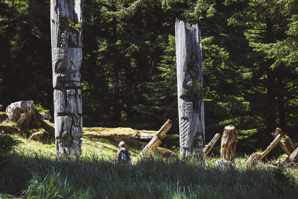 A woman standing between two old totem poles.
