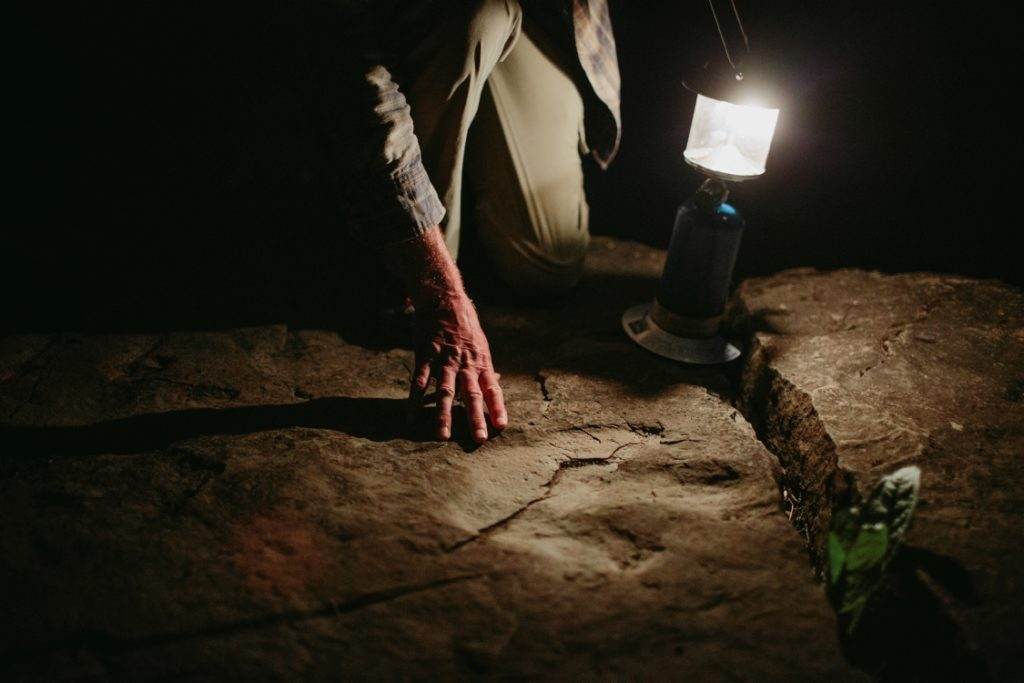 A lamp illuminates a fossilized footprint in a rock.