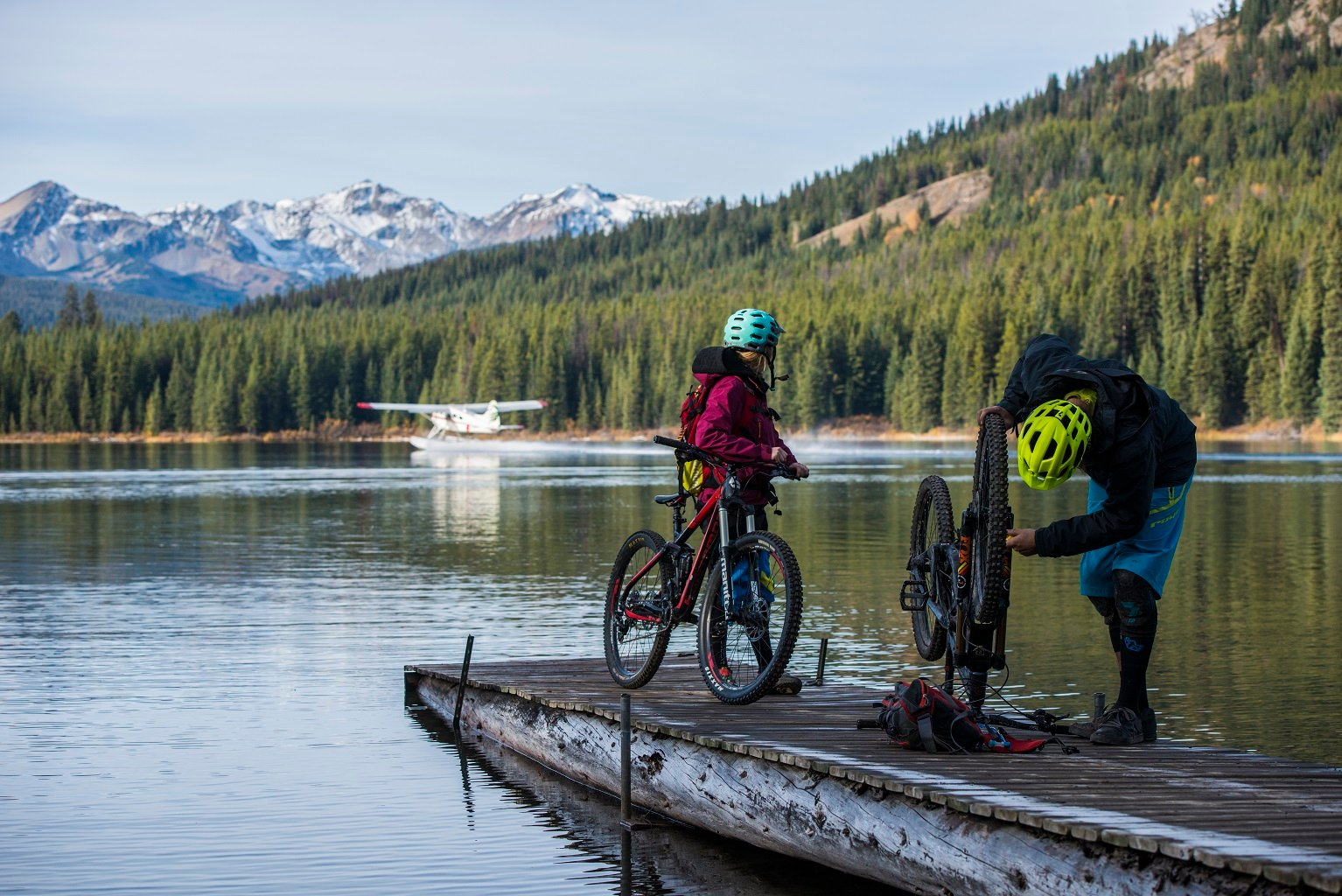 Two people with mountain bikes on a dock having been dropped off by a floatplane.