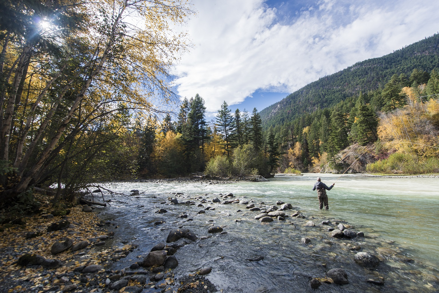 A man fishing with fall colours in the trees around him.