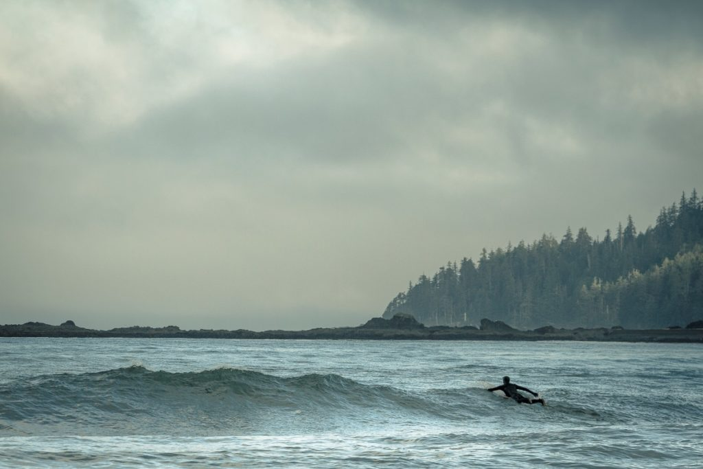 A surfer paddling out over the waves
