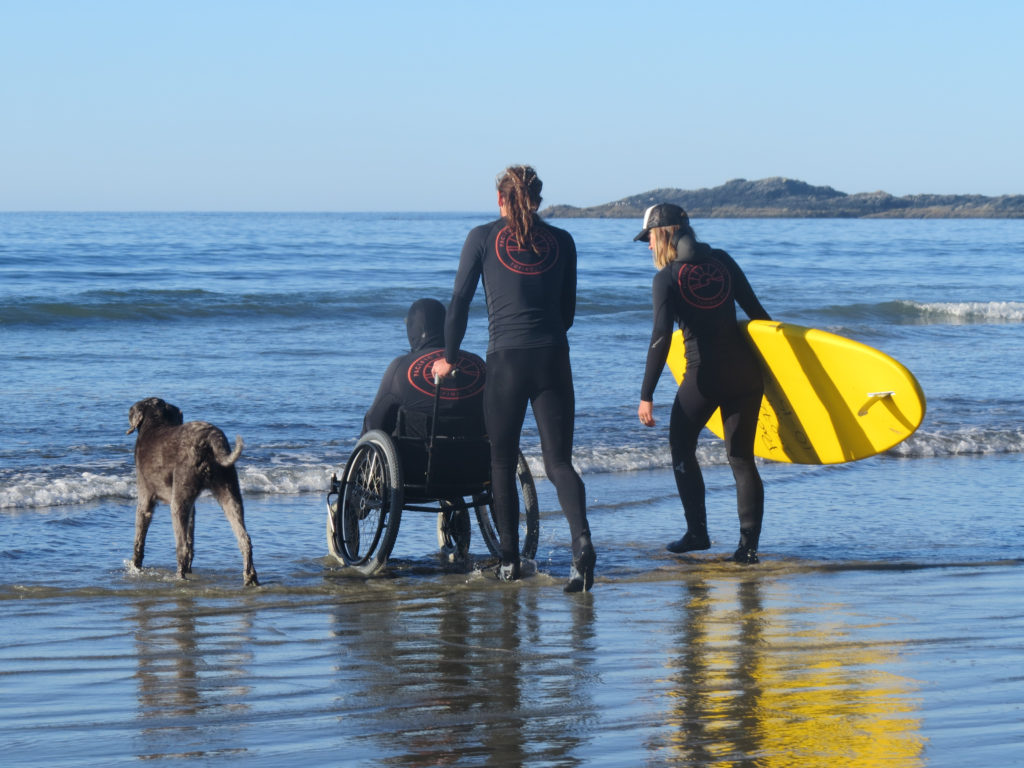 Two sufers wheeling a person in a wheelchair across the beach towards the ocean