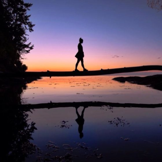 The silhouette of a woman walking across a fallen log at sunset.