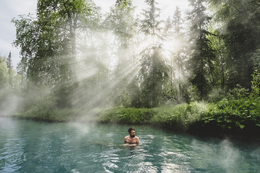 A man relaxed in a turquoise hot spring, drenched in sunlight.