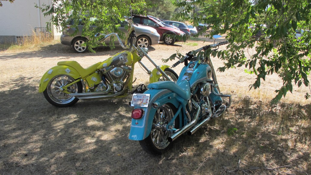 A bright yellow and bright blue motorcycle parked next to each other under a tree.