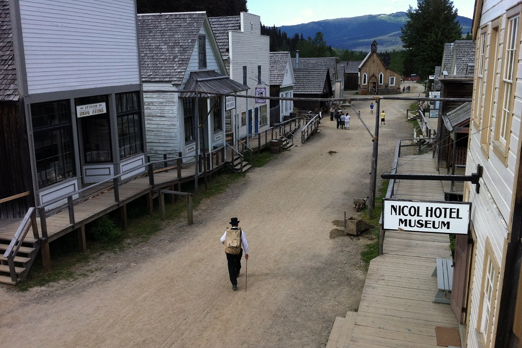 A man in a top hat walks down a dirt road lined with historic buildings.