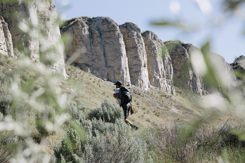 A man wearing a backpack hikes through a rocky landscape.