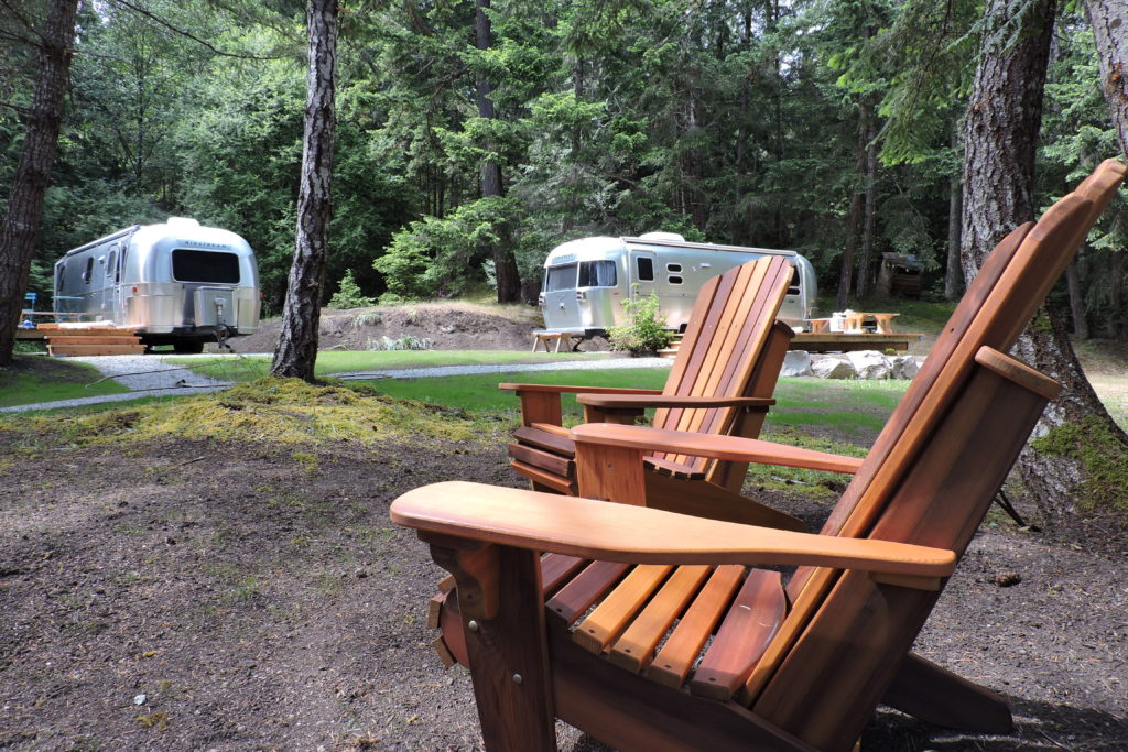 Two silver airstreams and two wooden chairs in a large camping space.