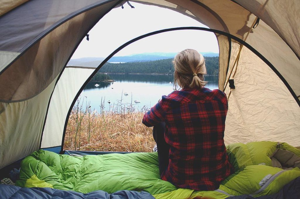 A woman in a plaid shirt sits in her tent, looking out over the water.