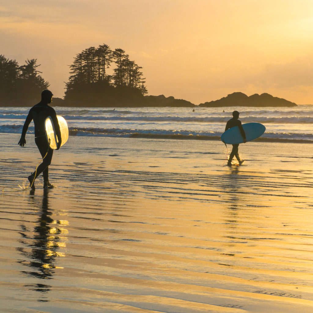 Two surfers carry their boards to the water under a golden sunrise.
