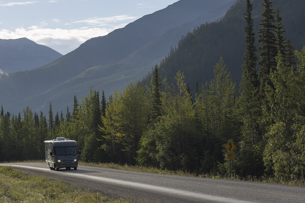 A RV travels down a tree-lined highway.