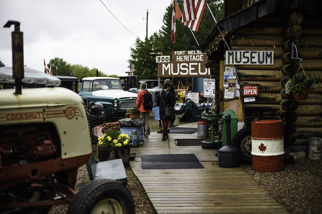 """Vehicles are parked in front of a log cabin with a sign that says """"Fort Nelson Heritage Museum""""."""